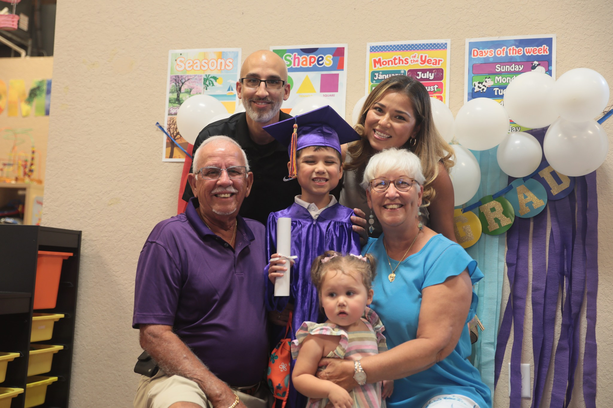 Child graduating preschool with their proud family
