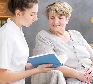 Caregiver Reading With Senior Woman
