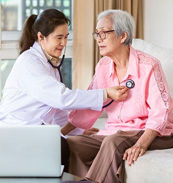 Caregiver Checking Senior Woman's Pulse