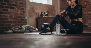 A woman in athletic attire sits on the floor of a workout studio, taking a rest and a water break.