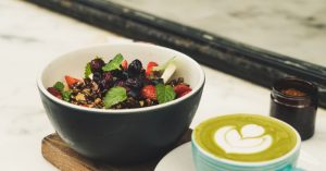 A blackberry fruit salad in a bowl next to green matcha latte in a blue mug. Photo by Paolo Nicolello on Unsplash.
