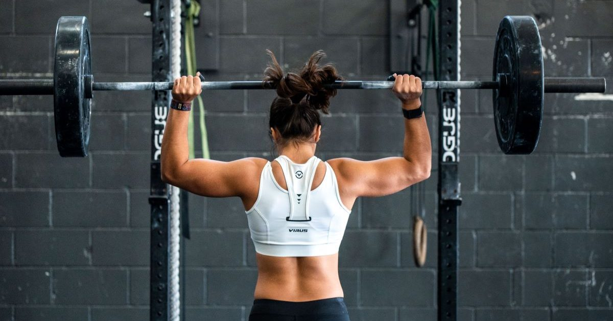 A woman doing weight lifting with a barbell and plates. Photo by John Arano on Unsplash