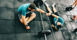 One man gives a fist bump to another after completing a workout together. Photo by Victor Freitas on Unsplash.