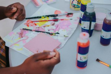 Child creating art using paintbrushes and watercolor paints.