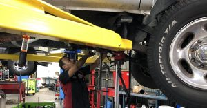A technician explores the underbelly of a vehicle.