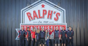 The Ralph's Technician team standing in front of a corrugated tin wall with the logo.