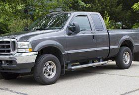 A grey truck on light grey pavement.