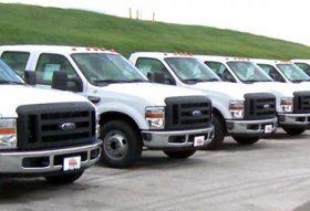 An image of a fleet of white trucks.