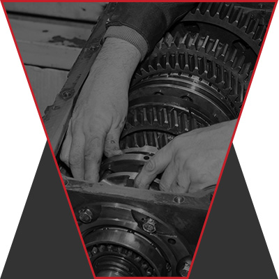 A black and white, designed image of a mechanic fiddling with car parts.