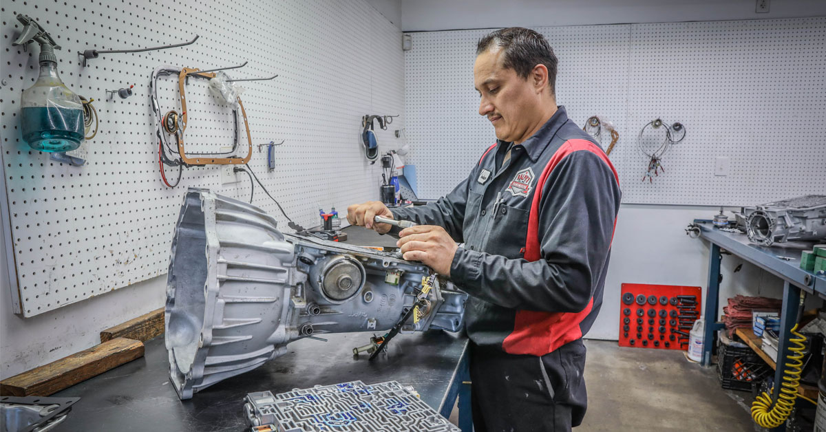 A Ralph's technician works on a part that is separated from the vehicle.