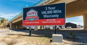"""A Ralph's Transmission billboard that reads """"3 year 100,000 mile warranty."""""""