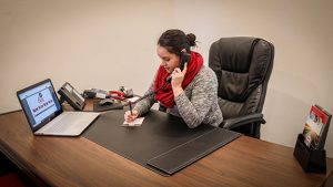 A woman works at a large desk on a phone.