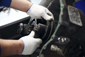 A man with soft, white gloves adjusts components in a vehicle.