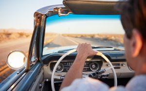 A person drives a classic 1950's car down an open desert road.