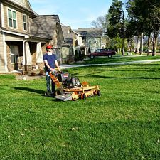 The owner of Ray Lawns mowing a large commercial housing lawn.