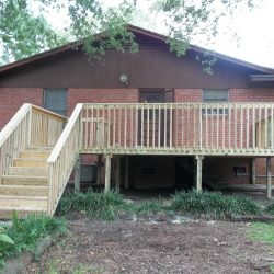 A brick house with a wooden deck with stairs in the back - Ready Decks