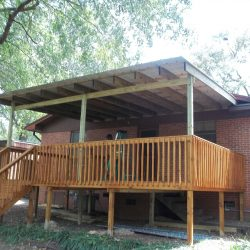 A covered deck with stairs on a brick house - Ready Decks