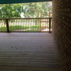 A large deck with railing off of a brick building - Ready Decks