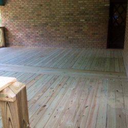 A wooden deck built off of a brick house - Ready Decks