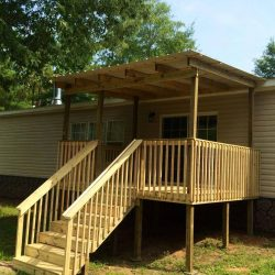 A raised covered porch with railing and stairs - Ready Decks
