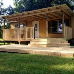 A beautiful covered porch with steps down to a patio - Ready Decks