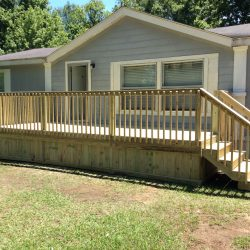 A rectangular deck with steps and wood skirting on a mobile home - Ready Decks