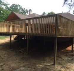 A tall deck with railing behind a house - Ready Decks