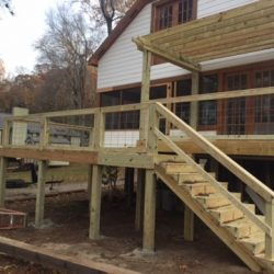 A raised deck with pergola, railing, and stairs - Ready Decks