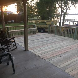 An add-on deck with railing, bench, and stairs off a house - Ready Decks