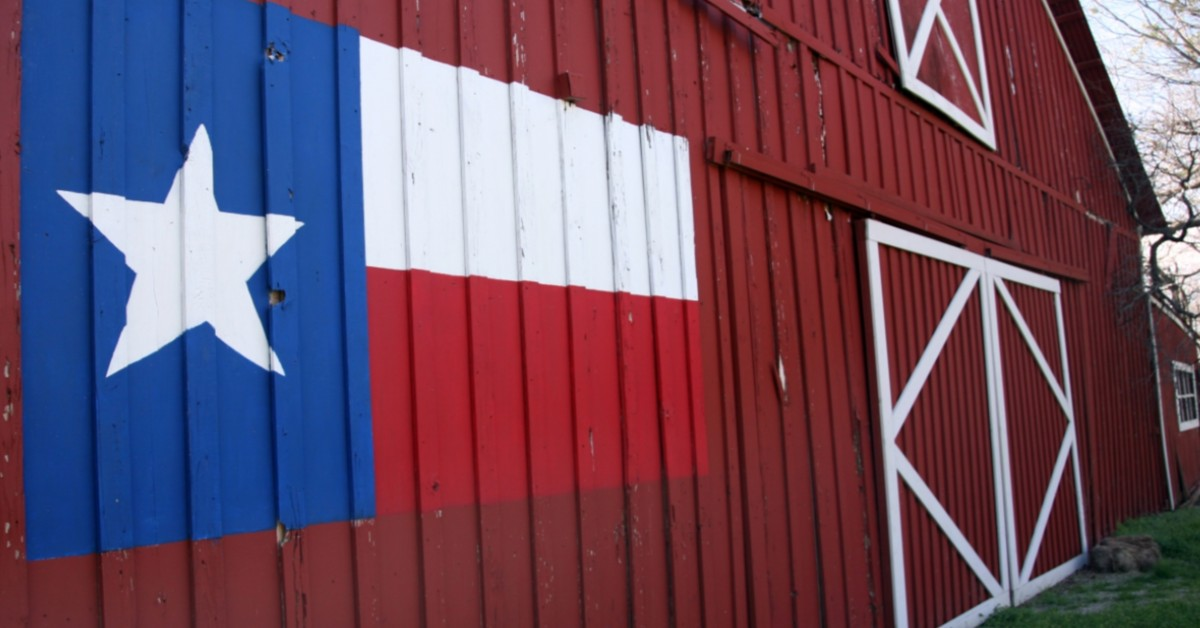 Photo of red barn with Texas flag painted on the side
