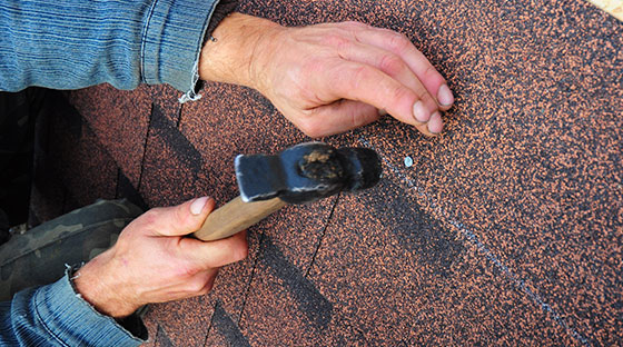Roofer Hammering Nail Into Shingles