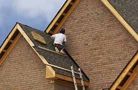 Roofer Installing Shingles on Brick Home
