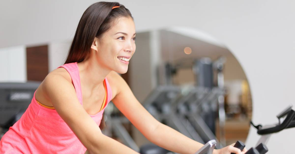 An image of a woman riding a spin bike.