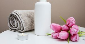 Rolled up towel, lit candle, pink flowers, and a cleanser.