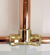 Image of a shiny T-shaped copper fixture