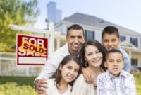 Image of a family posing in front of a sold sign
