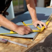 Image of worker using a pencil and protractor on materials