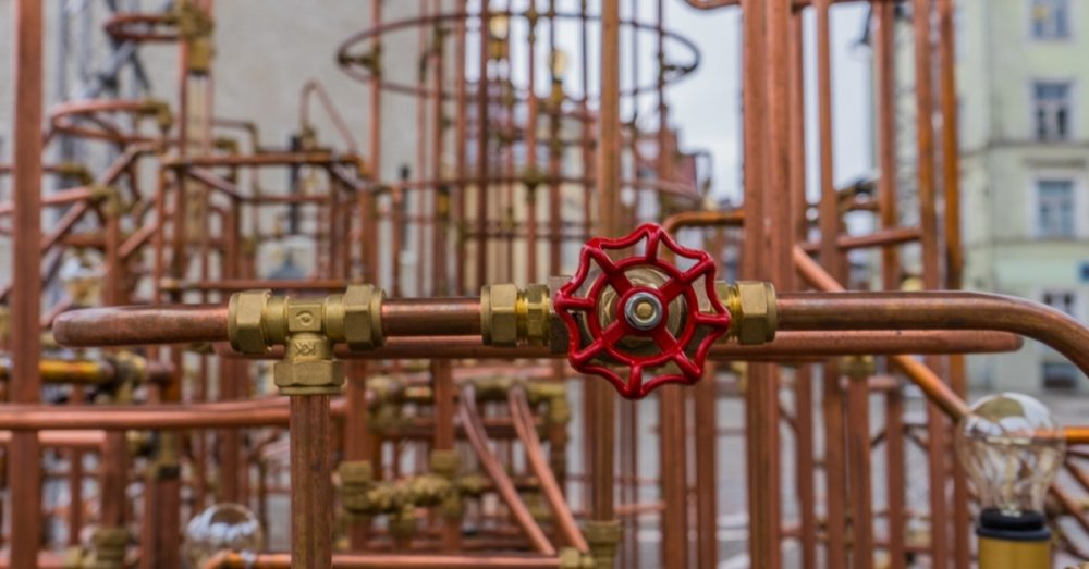 Image of red valve in an entanglement of piping inside a facility