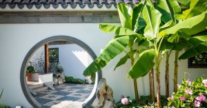 Green banana plants in front of a decorative entrance to a home's front patio. Pink flowers by the trees. Photo by vnwayne fan on Unsplash.