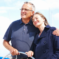 A senior couple stands at the helm of a small boat on a sunny but cloudy day