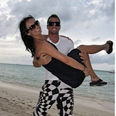 A man craddles a woman playfully in his arms while standing on a beach.