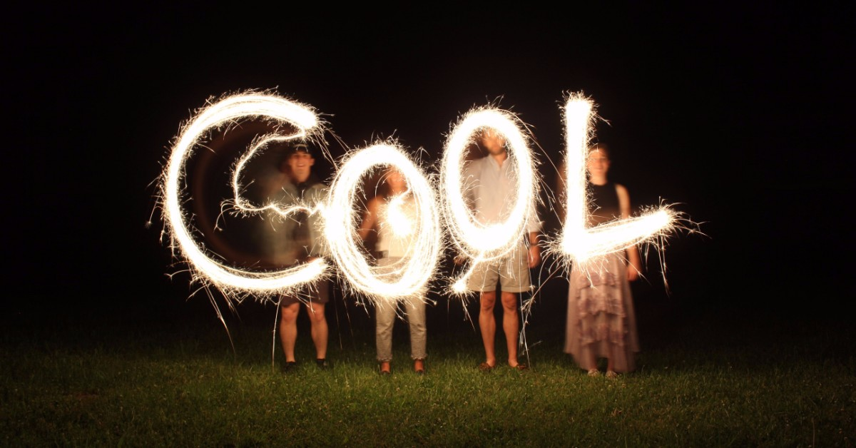 "Four people spelling out the word ""Cool"" with sparklers."