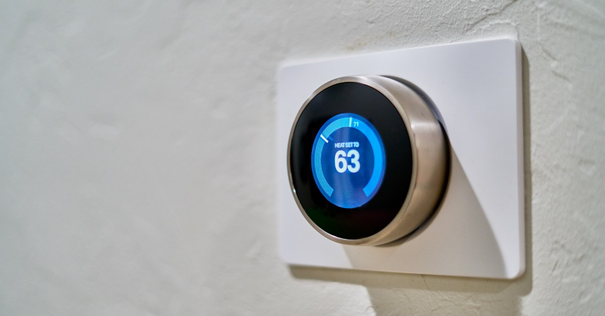 Blue electronic thermostat on white wall.