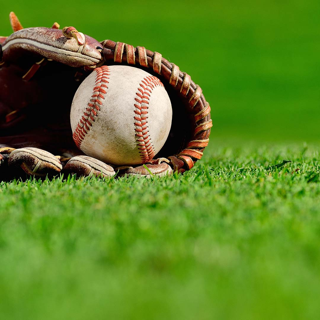 A baseball resting in a glove on a field.