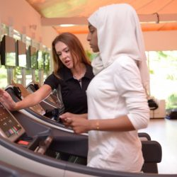 A woman works out with direction on a treadmill.
