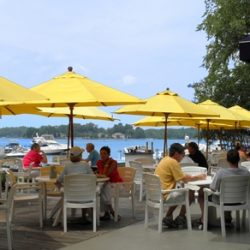 People sit at a lakeside cafe under bright yellow canapes.