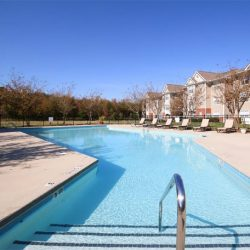 A photo that overlooks the length of the pool at Riverwalk Apartments from the ladder in.