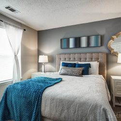 A small bedroom with with grey walls and white trim.