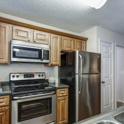 A narrow kitchen with medium-toned cabinets and nice appliances.