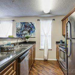 A narrow kitchen with modern, silver appliances.